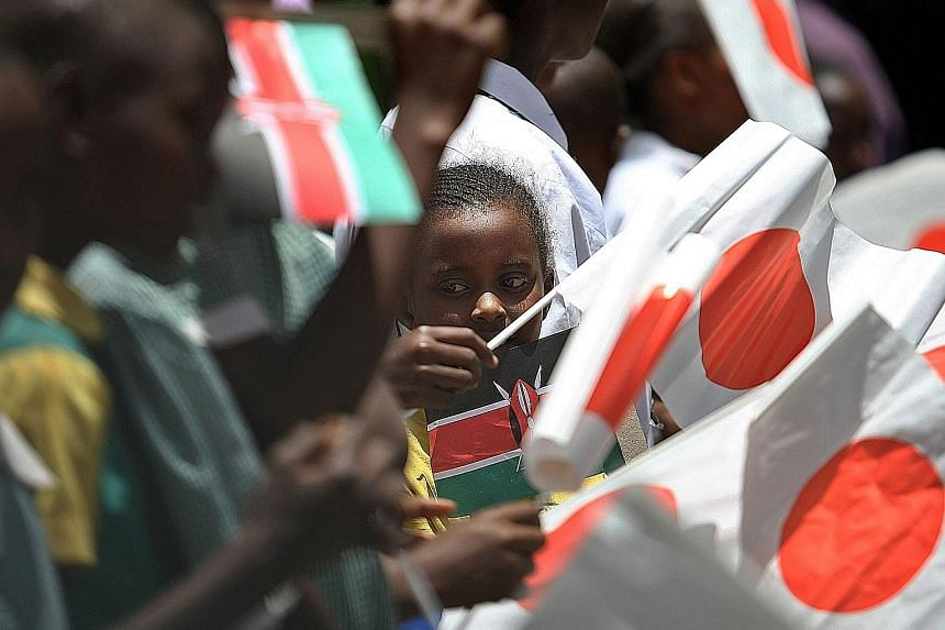 Kenyan children waving flags of their country and Japan during Japanese Crown Prince Naruhito's visit in 2010. Japan has pledged US$62 billion to Africa since 2013, a sum eclipsed by China's US$90 billion since 2012, but Japanese Prime Minister Shinz