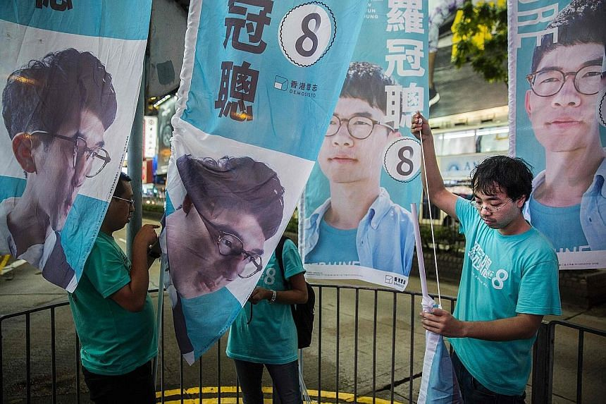 """Chief Executive Leung said he thinks the election results """"have nothing to do with the chances of anyone who aspires to be the next Chief Executive of Hong Kong"""". Supporters of Mr Nathan Law putting up flags in Causeway Bay following Mr Law's win in"""