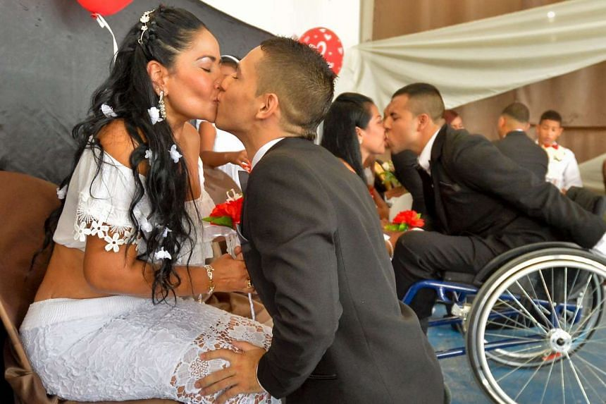 Couples kiss after getting married in a collective wedding ceremony at a prison in Cali, Colombia, in August 2016.