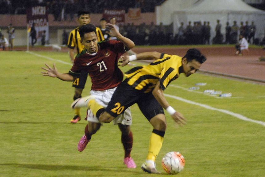 Indonesia's Andik Vermansyah (back) challenges Mohd Azrif Nasrulhaq Badrul Hisham of Malaysia during their friendly football match in Solo on Sept 6, 2016.