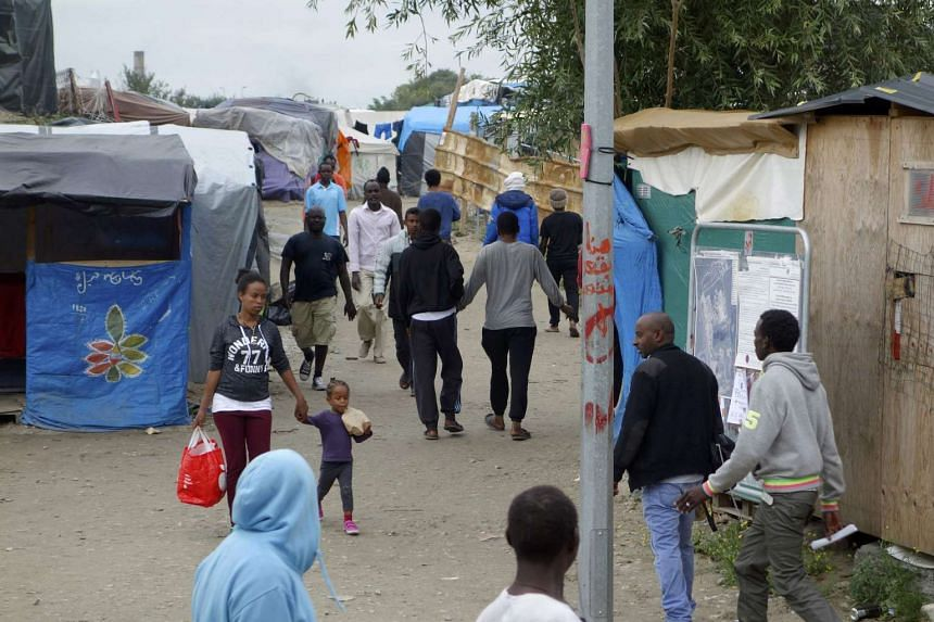 """Migrants walk in the northern area of the camp called the 'Jungle"""" in Calais, France on Sept 6, 2016."""