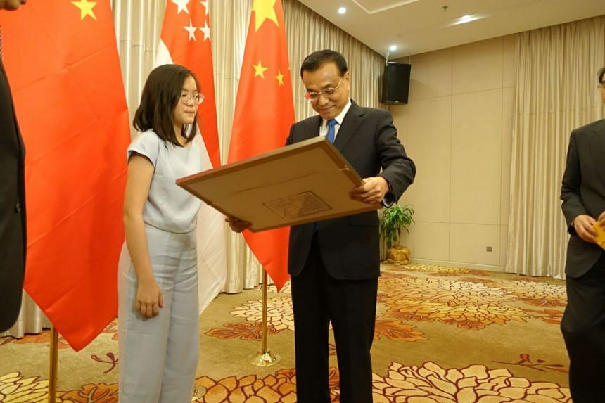 School of the Arts student Chin Ruisi, 16, presents her artwork to Chinese Premier Li Keqiang.