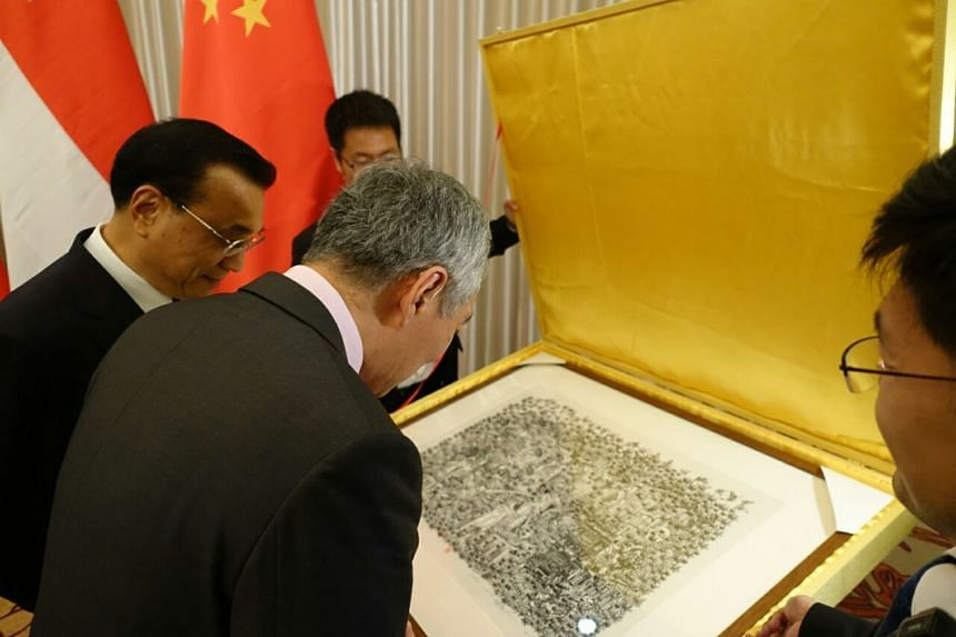 PM Lee checks out the details in the artwork given to Singapore by China with Premier Li (left). The work was created by Zhang Minjie, a Chinese artist.