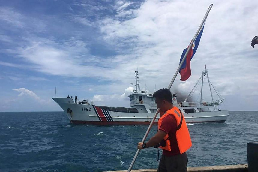 A Filipino activist holds a Philippine flag while a Chinese coast guard ship sails close by at the Scarborough Shoal on June 13, 2016.