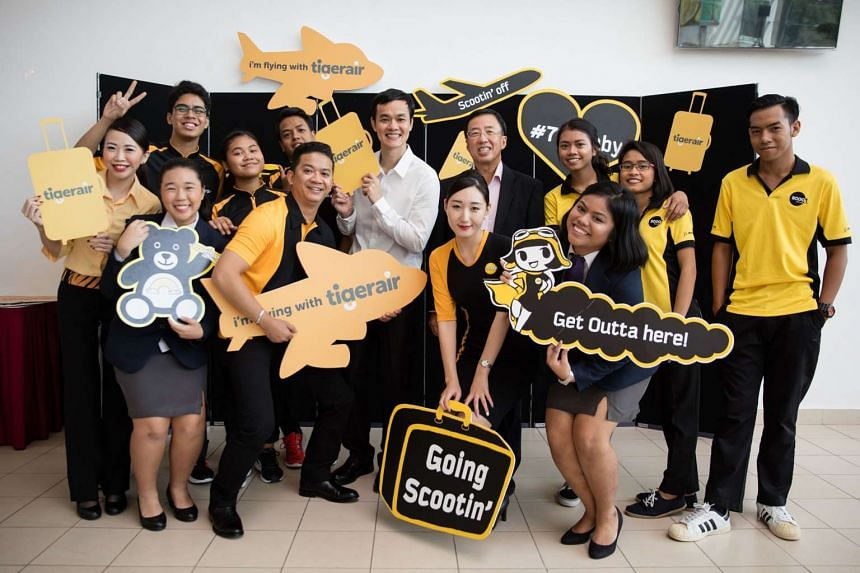 Mr Lee Lik Hsin, CEO of Budget Aviation Holdings (in white shirt) and Mr Bruce Poh, CEO of ITE (in black jacket), with ITE students and Scoot and Tigerair staff. Cabin crew interns joining next year will earn full-time pay.