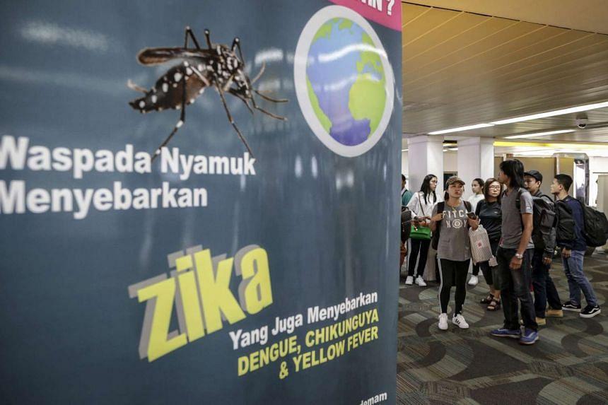 "Arriving passangers walk past a banner at Jakarta's Soekarno-Hatta International Airport with the writing ""Beware mosquitos cause Zika, dengue, chikunguya, and yellow fever""."