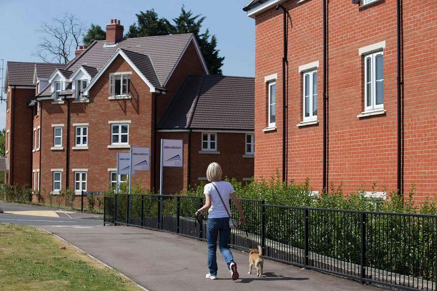 A woman walks her dog past sold new houses on a newly built housing estate in New Cardington, London on Aug 17, 2016.