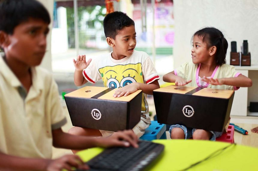 Muhammad Ashraf and his younger sister Nurul Umairah playing with mini-cajons, at Impresario Learning Lab, an after-school care centre in Jalan Bukit Ho Swee.