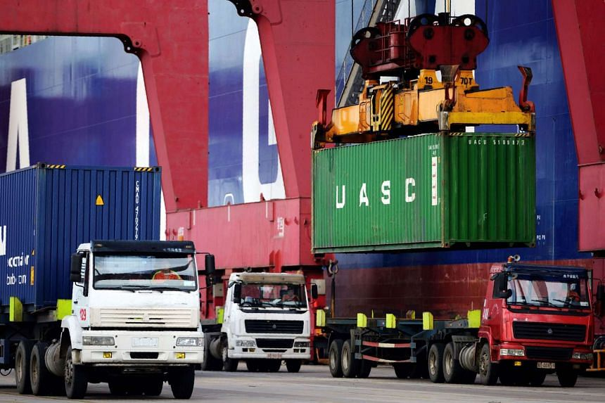 Trucks transport containers at a port in Qingdao, eastern China's Shandong province on Aug 8, 2016.