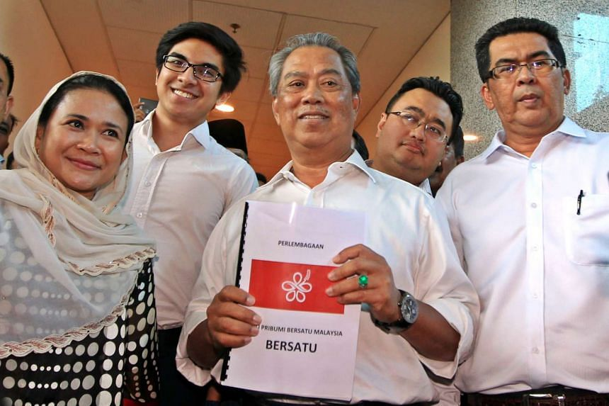 Mr Tan Sri Muhyiddin holding a proposed logo for the new Parti Pribumi Bersatu Malaysia with several of its interim leaders after applying to register it.