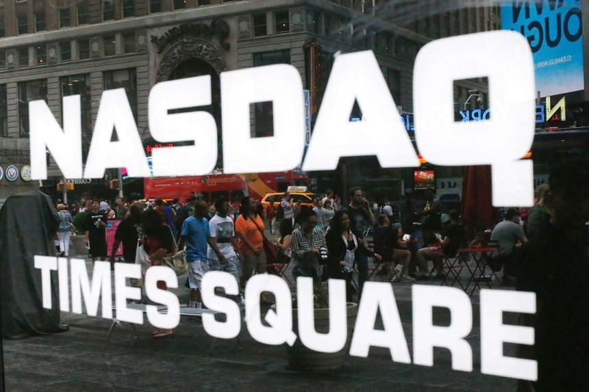 This file photo taken on June 16, 2015 shows people walking past the Nasdaq MarketSite in New York's Times Square in New York City.
