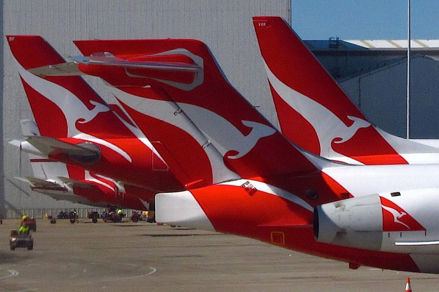 A member of the ground staff drives past a group of Qantas planes parked at the Qantas Domestic Terminal located at Sydney Airport, Australia on July 26, 2016.