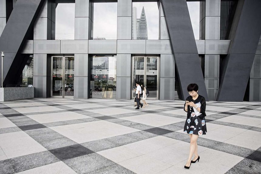 People walk past the entrance to the Shenzhen Stock Exchange building in Shenzhen, China, on Aug 23, 2016.
