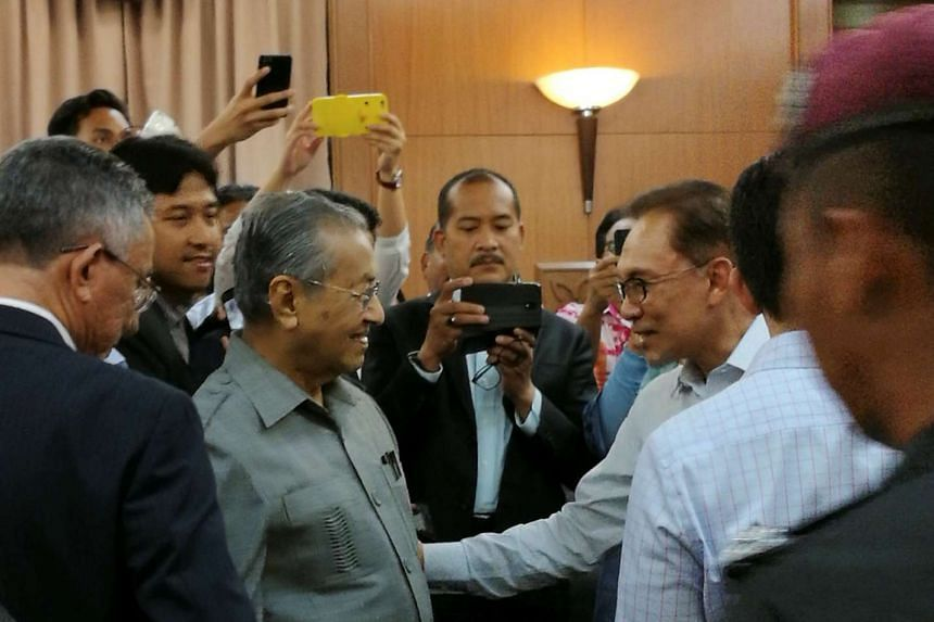 Malaysia's former prime minister Mahathir Mohamad (centre left) meets with jailed opposition leader Anwar Ibrahim (centre right) in a high court in Kuala Lumpur on Sept 5, 2016.