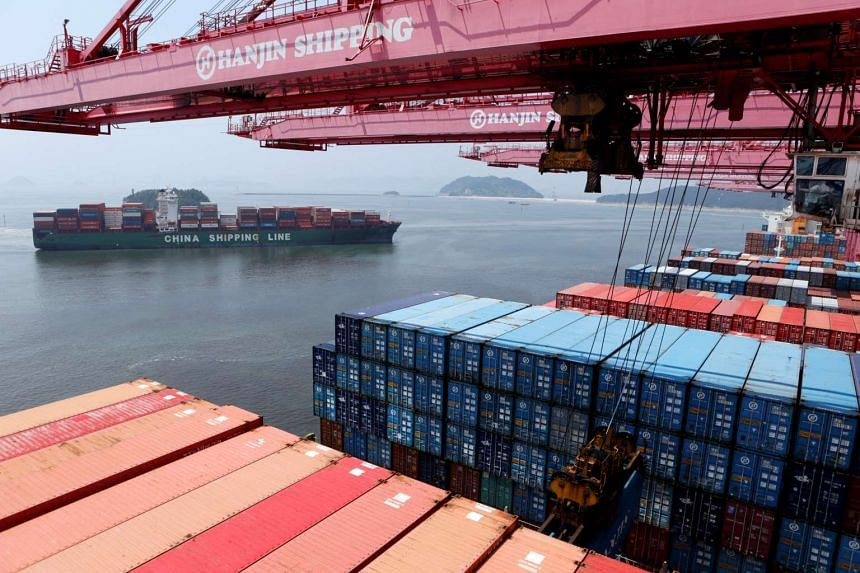 A crane carries a container from a Hanjin Shipping ship at the Hanjin container terminal as a China Shipping Line ship (left) arrives at the Busan New Port in Busan in August 2013.