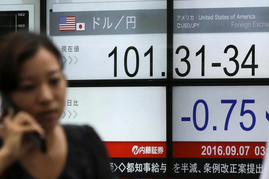 A cyclist using a mobile phone is running past a display showing the exchange rate between US dollar and Japanese yen during an afternoon trading session in Tokyo on Sept 7, 2016.