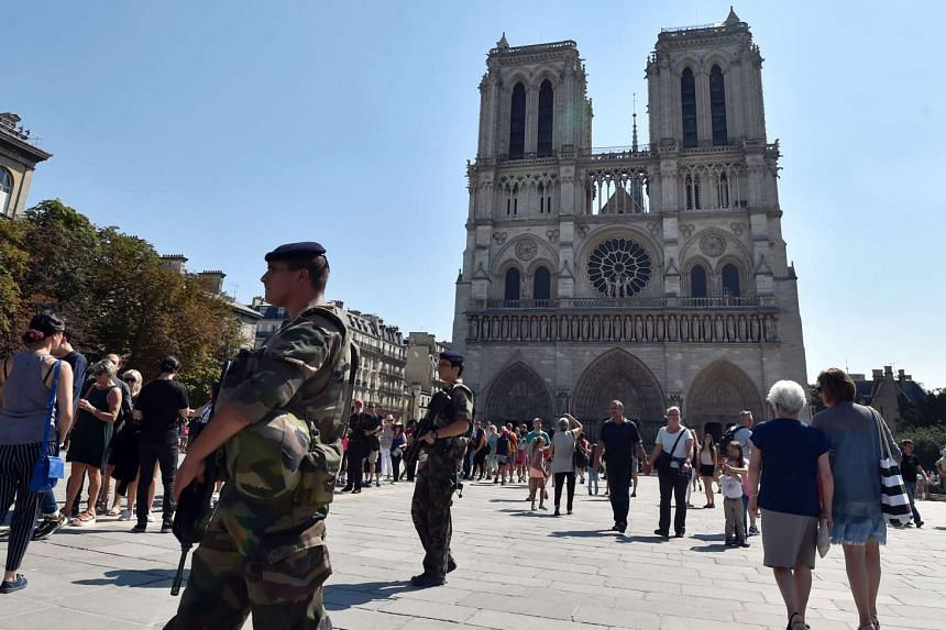 French soldiers patrolling in front of Notre Dame cathedral in Paris as part of the Sentinelle military force security mission while people queue for the mass for the feast of the Assumption on Aug 15, 2016.