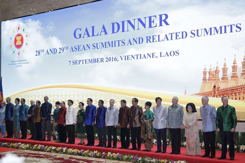 The leaders and their spouses having a group photo taken at the Asean Summits gala dinner.