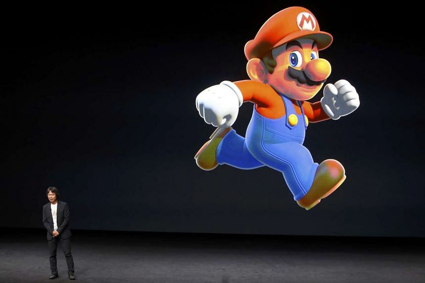 Shigeru Miyamoto stands next to the Super Mario character during an Apple media event in San Francisco.