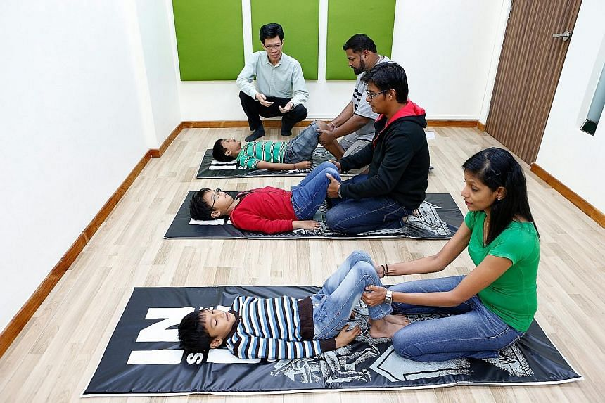Parents assist their children as they perfom body movement exercises believed to stimulate brain development - part of the KidsBright programme by Care Corner Singapore for children with learning difficulties. The welfare organisation has offered thi