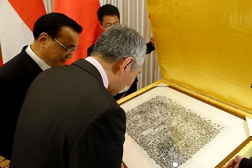 Prime Minister Lee Hsien Loong looking at a print of Singapore scenes presented to him by his Chinese counterpart Li Keqiang. Mr Lee received the 36cm by 49cm artwork by Chinese artist Zhang Minjie - featuring HDB flats, the Merlion, Marina Bay Sands