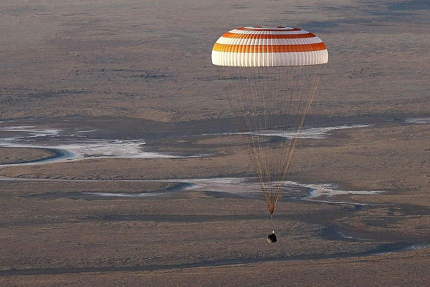 Disappearing into a layer of haze (above) as it approached the ground, the Soyuz TMA-20M spacecraft capsule carrying (left, from top) United States astronaut Jeff Williams, and Russian cosmonauts Oleg Skripochka and Alexey Ovchinin landed south-east