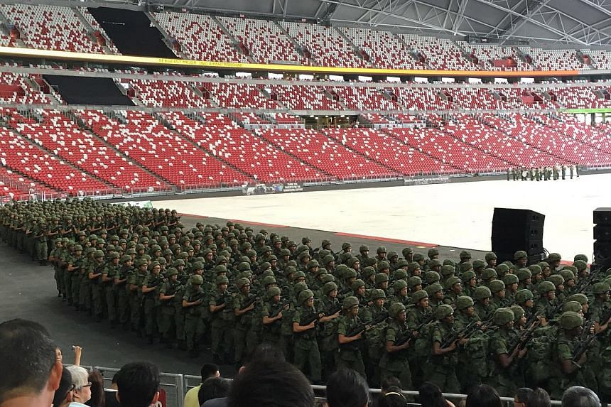 Recruits from the Basic Military Training Centre and the 3rd Battalion of the Singapore Guards at the stadium during their passing-out parade yesterday, watched by family members and friends.
