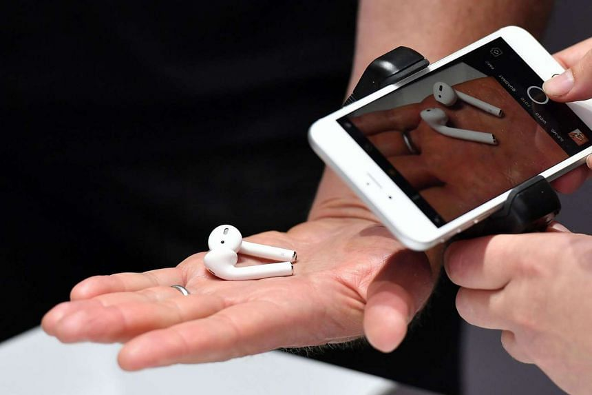 A person takes a photo of a set of wireless Apple AirPods during a media event at Bill Graham Civic Auditorium in San Francisco, California on Sept 7, 2016.