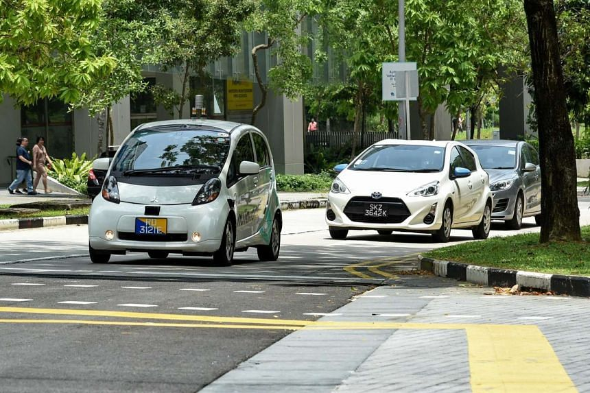 A driverless car (left) is seen on a trial test on the road in Singapore on Aug 29, 2016.