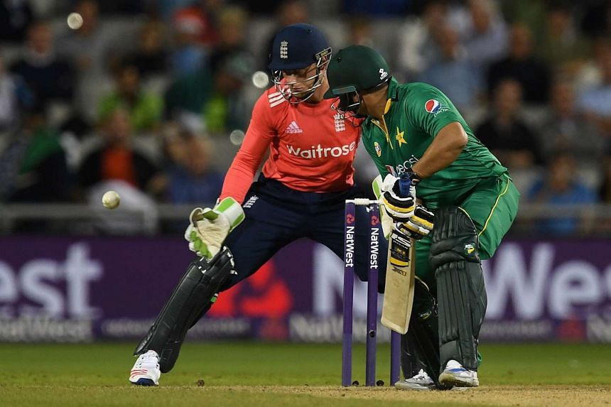 Pakistan's Babar Azam plays a shot past England's Jos Buttler during the T20 international cricket match between England and Pakistan at The Emirates Old Trafford, in Manchester, north-west England, on Sept 7.