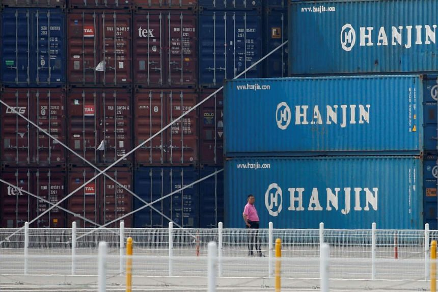 A man stands in front of shipping containers at the Hanjin Shipping container terminal at Incheon New Port in Incheon on Sept 7.