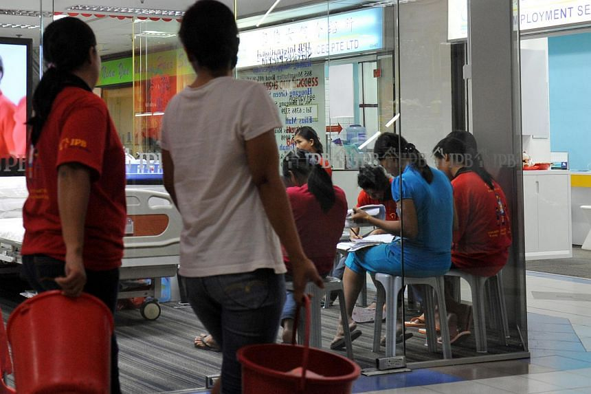Maids undergoing training are seen seated inside a maid agency in Bukit Timah.
