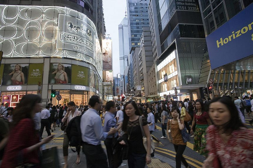 Pedestrians walk past a Coach and Gap store on Queen's Road in the Central district in Hong Kong.