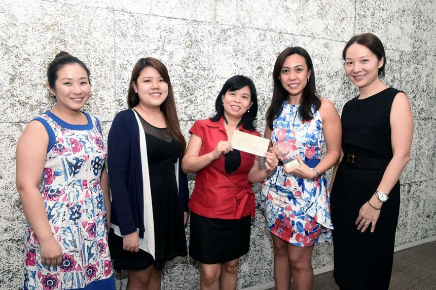 Representatives from investment firm 8I Holdings (from left) Goh Yi Lin, Cherie Lim, Pauline Teo and Nga Hui En with The Straits Times School Pocket Money Fund general manager Tan Bee Heong (centre, in red).