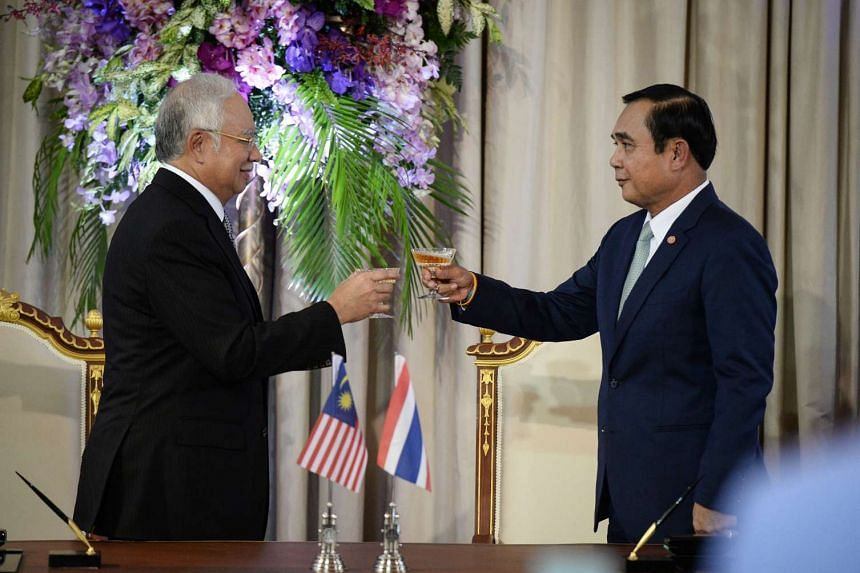 Malaysian Prime Minister Najib Razak (left) raises a glass with Thai Prime Minister Prayuth Chan-Ocha at the Government House in Bangkok on Sept 9, 2016.
