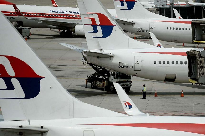 Malaysia Airlines ground staff walk past Malaysia Airlines aircraft parked on the tarmac at the Kuala Lumpur International Airport in Sepang on June 20, 2016.