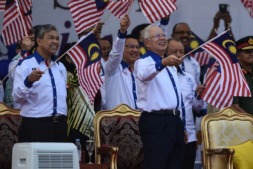 Malaysia's Prime Minister Najib Razak (right) and his deputy Ahmad Zahid Hamidi (left) wave national flags during the 59th National Day celebrations at Independence Square in Kuala Lumpur on Aug 31, 2016.
