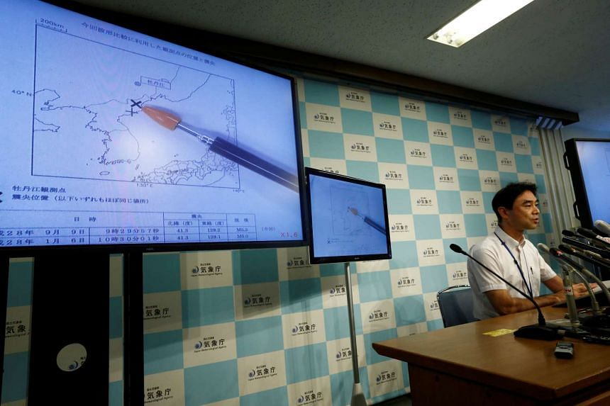 The Japan Meteorological Agency's earthquake and tsunami observations division director Gen Aoki speaking next to screens showing the seismic event was indicated on North Korea and observed in Japan during a news conference at the Japan Meteorologica