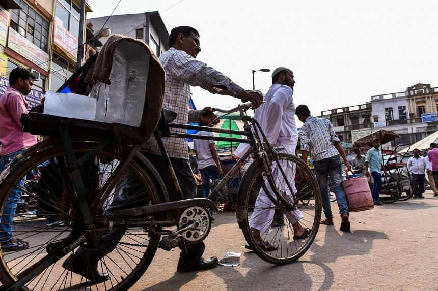 Ram Babu, 52, pushes his bicycle laden with blocks of ice in the old quarters of New Delhi on June 4, 2016.