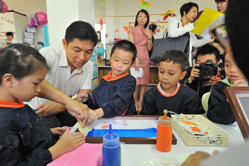 Mr Tan Chuan-Jin (second from left) doing silkscreen printing with children at My First Skool at Blk 1 Haig Road on Sept 9, 2016.