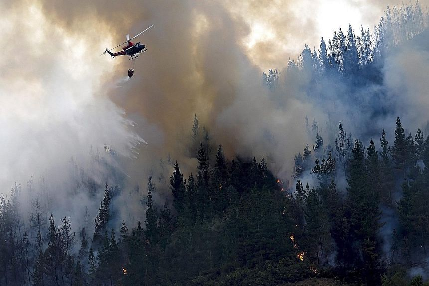 A helicopter dropping water on a forest fire near the village of A Fonsagra, in the Galicia region of north-western Spain, on Wednesday. The fire has already burned at least 80ha of forest.