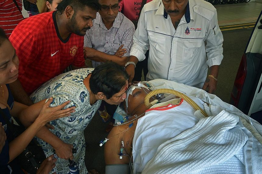 Above: Madam Thanabagiyam kissing her son, Mr Manokaran, as he was being wheeled into the emergency department at NUH yesterday. Left: Madam Muniandy, Mr Manokaran's wife, who was also in the crash, had a hairline fracture in her spine.