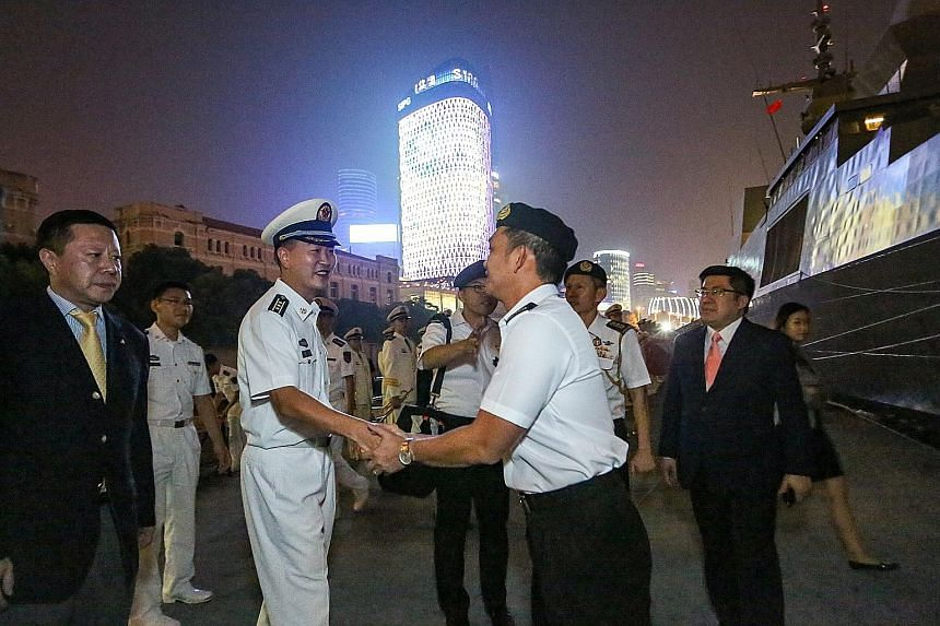 RSS Steadfast being welcomed by Chinese naval officers in Shanghai yesterday. This is the warship's second port call in Shanghai, the first being in 2008. Singapore's Col Cheong (at right) being welcomed yesterday by PLA Navy's Captain Lu Xing, the d