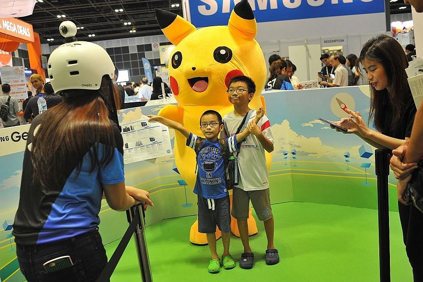 Optimus Seah (in blue), six, and Remus Seah, 10, posing for a photo yesterday with a Pikachu mascot at the Samsung booth, which is promoting the Samsung Gear360.