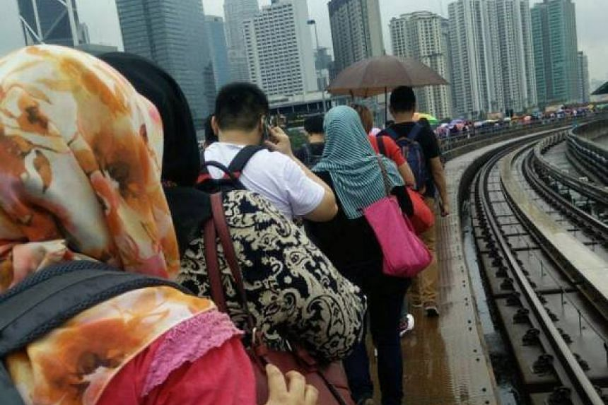 Commuters walking on the LRT tracks in KL on Sept 9, 2016.
