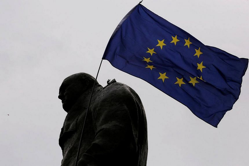 A European Union flag is waved over a statue of former Prime Minister Winston Churchill as demonstrators protest during a March for Europe against Brexit in London on Sept 3, 2016.