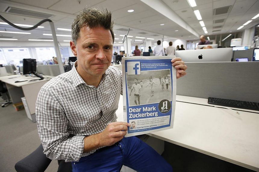 Aftenposten's editor-in-chief and CEO Espen Egil Hansen poses with the day's edition of Aftenposten featuring the iconic picture from the Vietnam war, taken by Nick Ut on Sept 9, 2016.