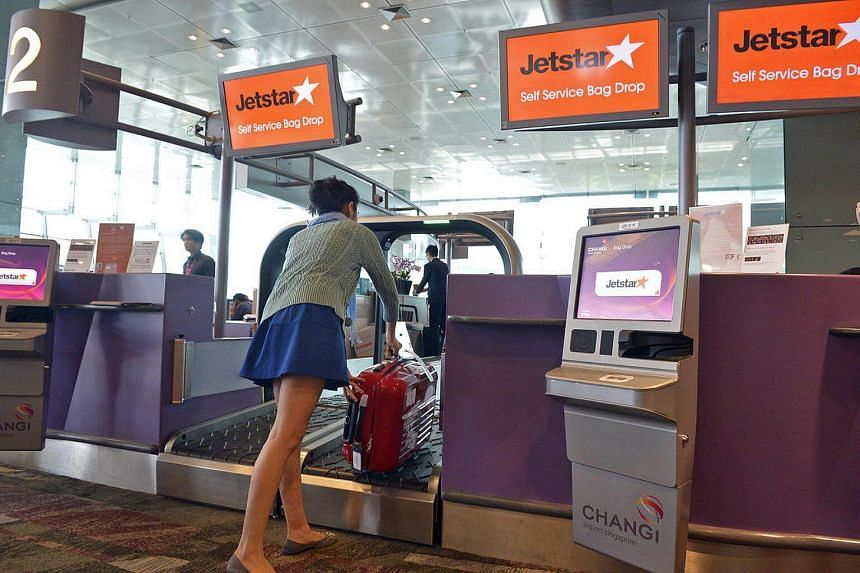 A Jetstar passenger drops her luggage at the designated area at Changi Airport Terminal 1. Budget carriers are becoming more flexible to attract a growing number of business travellers.