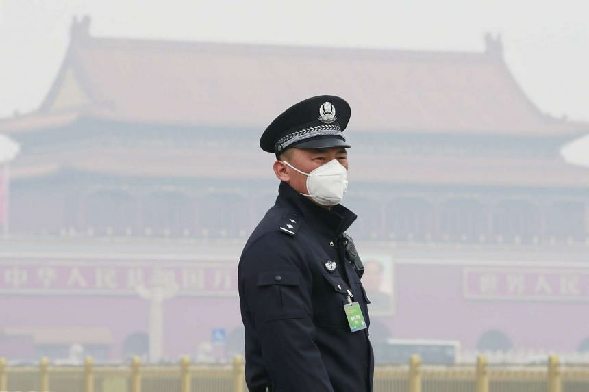 A policeman, wearing a mask against severe pollution, on duty in Beijing, on March 3, 2016.