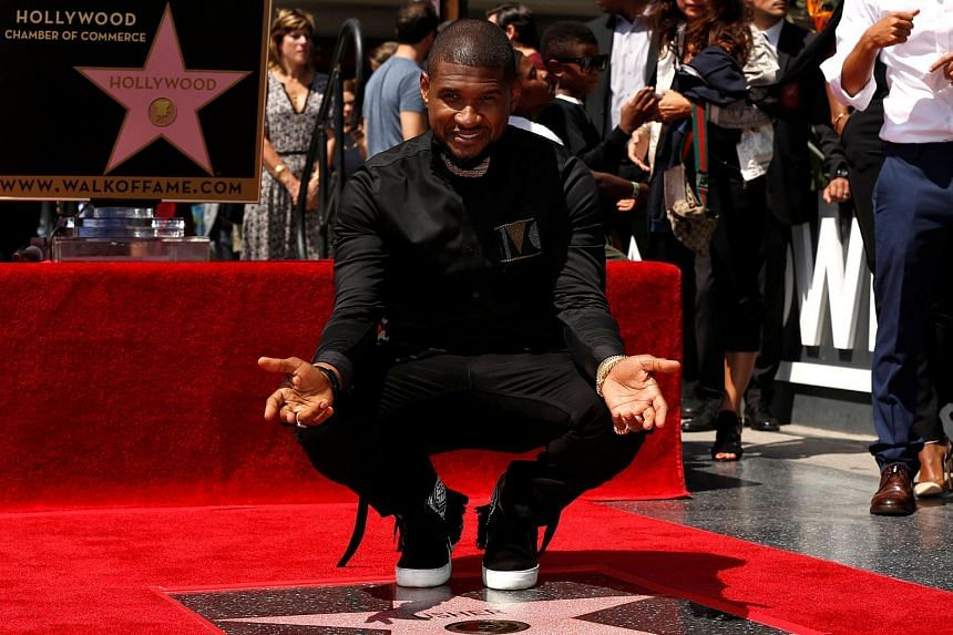 Recording artist Usher poses on his star after it was unveiled on the Hollywood Walk of Fame in Los Angeles, US on Sept 7, 2016.